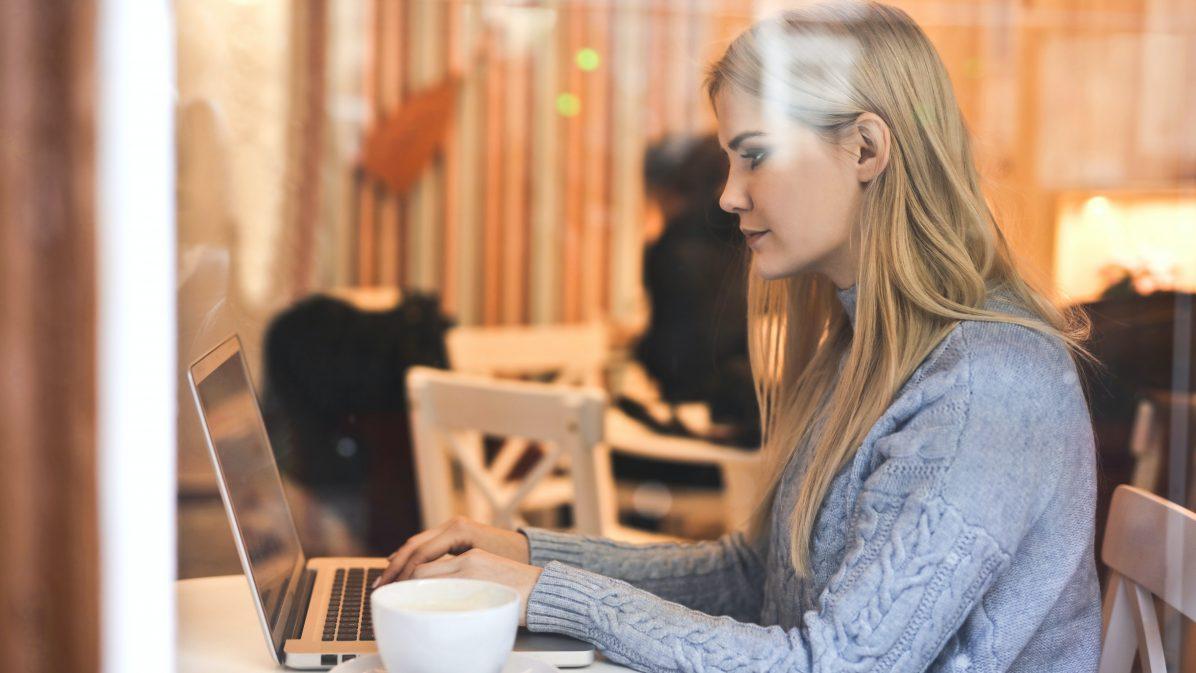 Ung kvinna arbetar vid datorn
